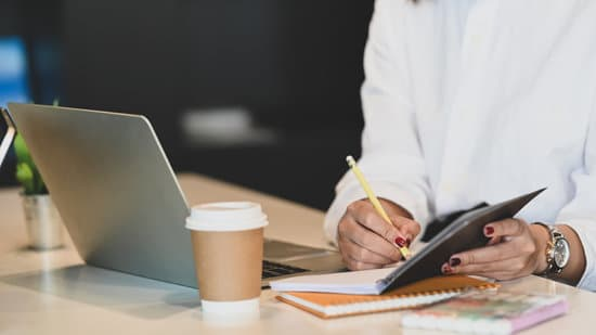 Cropped image waist up of businesswoman taking notes/writing on notebook that putting on white working table with coffee cup, computer laptop and potted plant over office as background.