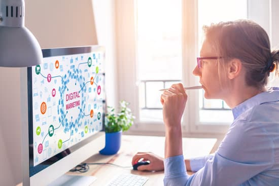 Woman using computer with digital marketing technology concept on the screen with icons about email and social media network advertising and analytics