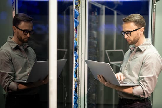 Serious busy young IT engineer with beard standing by server cabinet and using laptop while providing network support