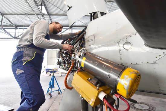 Aircraft mechanic repairs an aircraft engine in an airport hangar