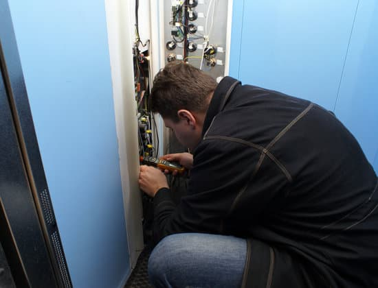 mechanic repairing button in the lift located in a residential building