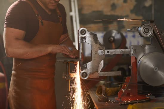 Busy blacksmith in leather apron adjusting detail on flat grinding machine while shaping it in workshop