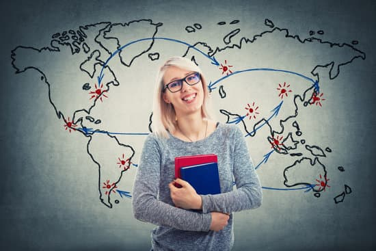Young woman wearing glasses and holding two books over world map background. Global education concept. Cheerful student girl planning her next point on map to continue studying.
