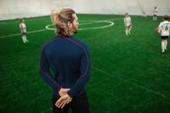Rear view of football trainer in activewear standing on field and watching for players