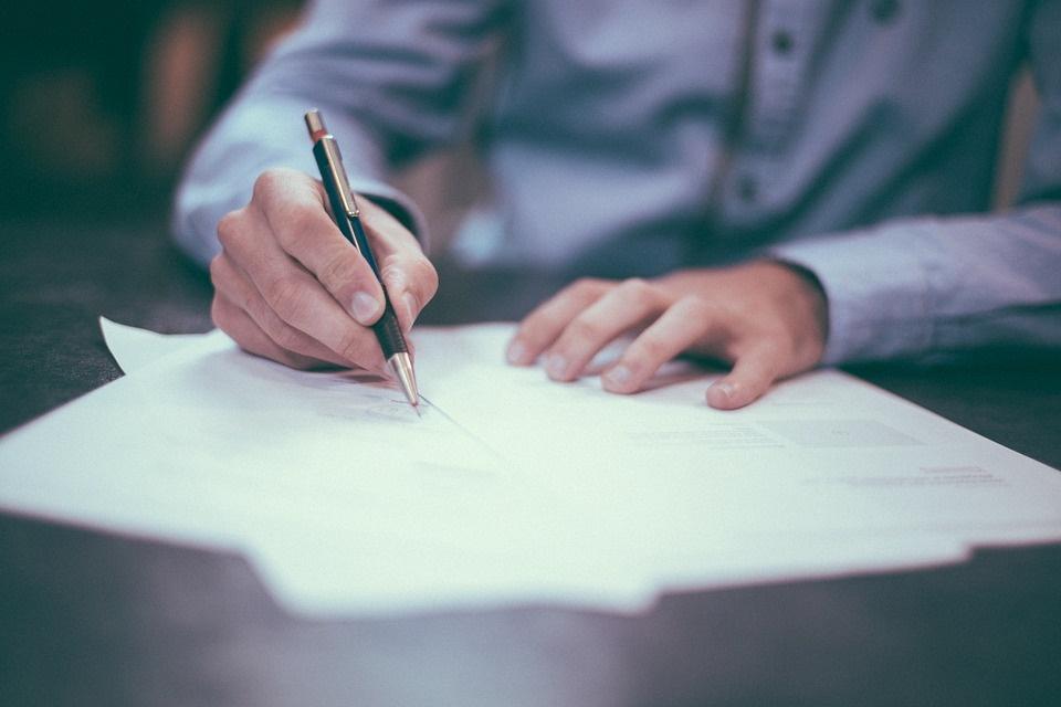 man writing on paper - collegecliffs