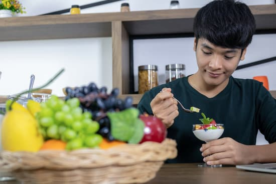 A handsome young Asian man is happy and is eating fruit yoghurt in the modern restaurant. Health care concept