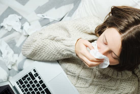 A young woman lies in bed with a laptop and blows her nose in a napkin. Seasonal cold or flu concept