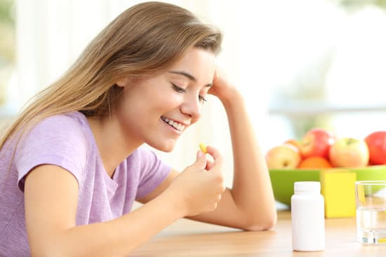 Happy teen taking a omega 3 vitamin pill on a table at home