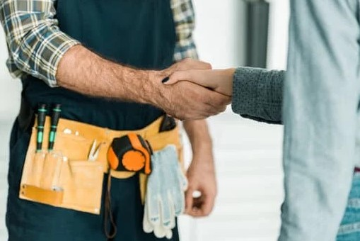 Plumber shaking hands with customer