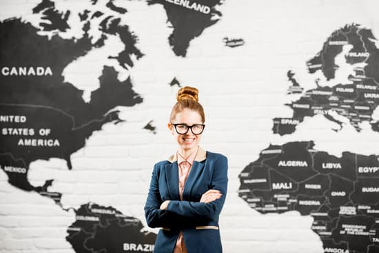 Portrait of a female travel agent dressed in the suit standing indoors on the world map background