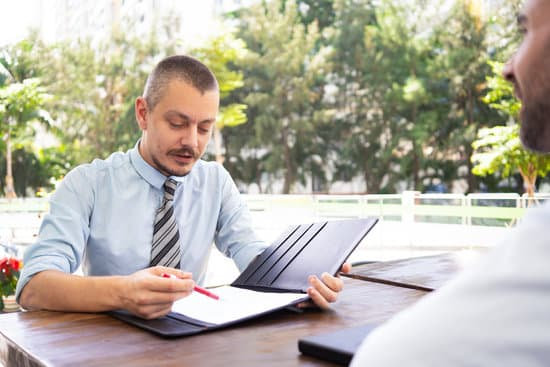 Serious hr manager asking questions to candidate at interview. Mature executive sitting at cafe table and reading contract to client. Recruitment or partnership concept