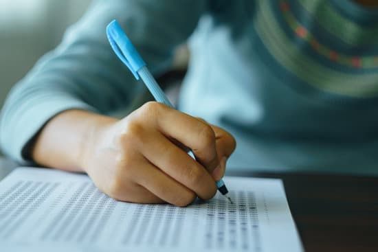 Close up of high school or university student holding a pen writing on answer sheet paper in the examination room. College students answering multiple choice questions test in the testing room in university.