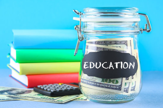 Bank with dollars and calculator, books on a gray background. Finance, moneybox, education