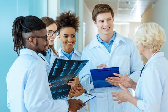 A multiracial group of young medical interns listening to a elder doctor in a hospital corridor