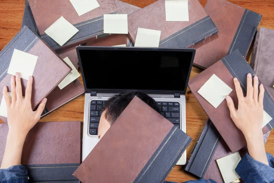 Photo of male college student sleeping above laptop after doing school work with books