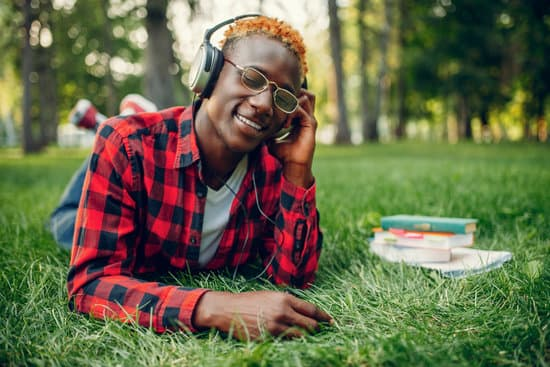 Black student in headphones resting on the grass in summer park. A teenager studying and leisures outdoors