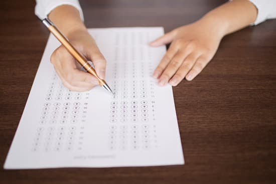 Close-up of female hand holding pen and marking answers in questionnaire form. Student doing examination test