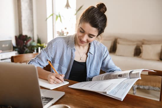Image of positive pretty woman 20s in casual clothing writing down notes on paper and using laptop while working in flat