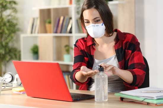 Student woman with protective mask applying hand sanitizer avoiding covid-19 sitting on a desk at home