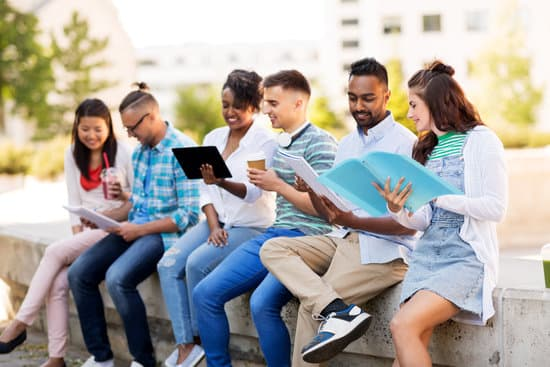 education, international and technology concept - group of happy exchange students with notebooks and tablet pc computer outdoors